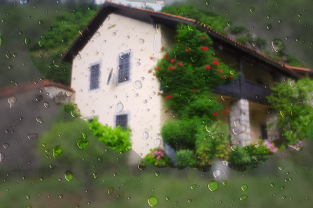 Raindrops on window glass and a house