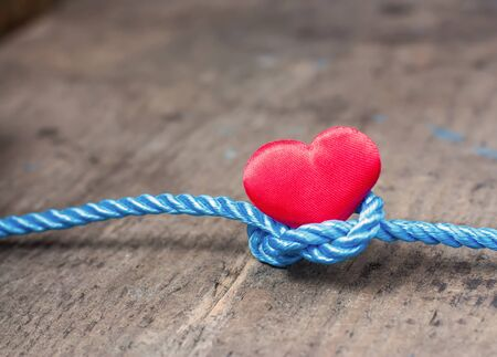 Red heart with a bundle on a wooden board Stock Photo