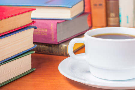 scientific literature: Studying scientific literature in the library with and drinking coffee Stock Photo