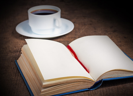 Open book with blank pages with a cup of coffee on a wooden surface photo