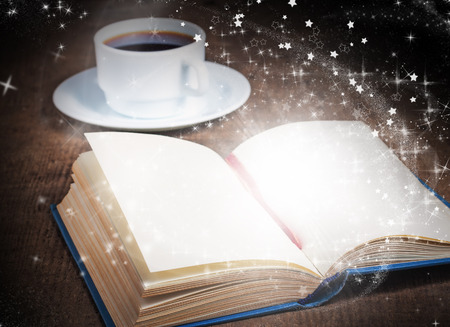 Open magic book with sparks and light and a cup of coffee on a wooden surface photo