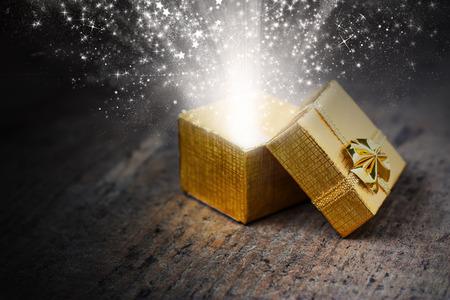 magia: Regalo m�gico abierto con los rayos y chispas en primer plano en una superficie de madera Foto de archivo