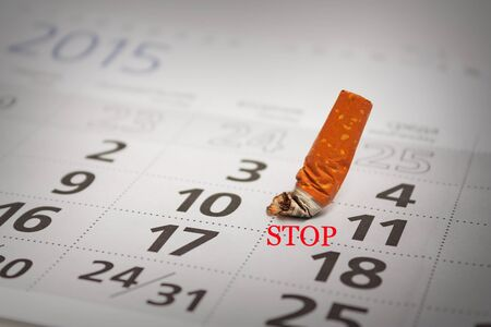 Extinguished cigarette butt on the calendar. Stop smoking now