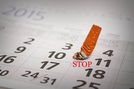 Teint mégot de cigarette sur le calendrier. Arrêter de fumer maintenant Banque d'images - 41675717