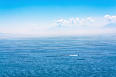 Blue water surface of the sea and the mountains on the horizon