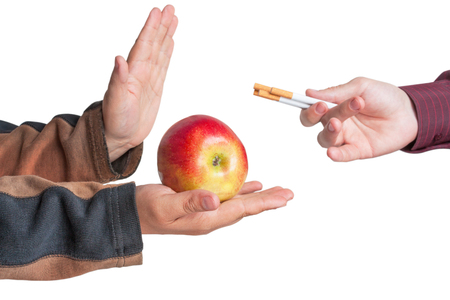 Man refuse the offer of cigarettes and give to another person apple isolated Stock Photo