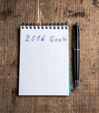 achieve goal: Notebook with pen on wooden background and goals of year 2016