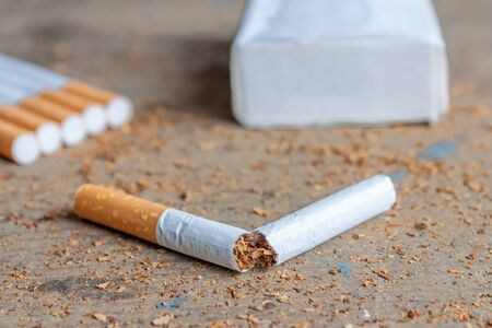 anti tobacco: Anti-smoking background with broken cigarettes on wooden surface. Stop smoking now Stock Photo
