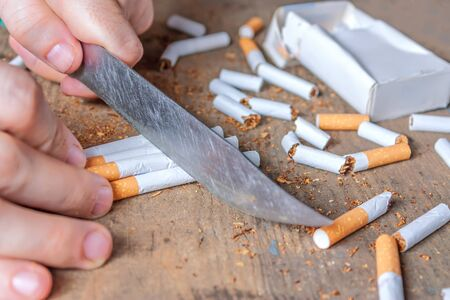anti tobacco: Anti-smoking conceptual background. Sliced cigarettes on the table. Giving up smoking Stock Photo
