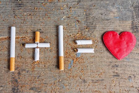 diseased: Cigarettes and diseased heart on wooden surface Stock Photo