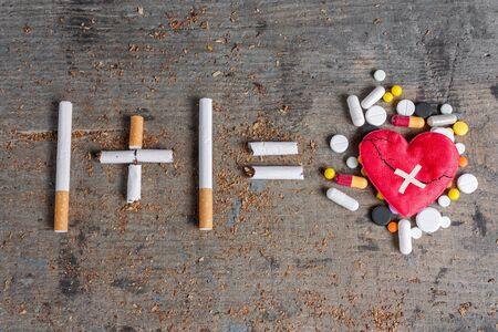 anti smoking: Antismoking background. Diseased heart and pills on wooden surface. Stop smoking now Stock Photo