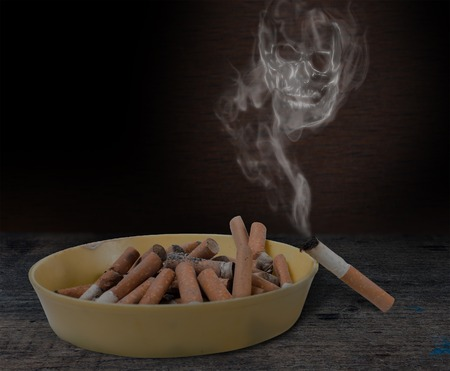 anti smoking: Pile of cigarette butts in the ashtray and the skull of the smoke. Quit smoking now