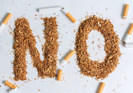 Broken cigarettes and tobacco on white background. Quit smoking now