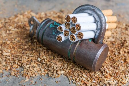 Conceptual antismoking background with broken cigarettes and a padlock. Quit smoking now