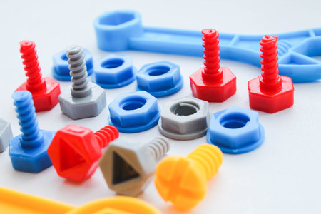 Childrens plastic multi-colored toy bolts and nuts. A set of construction hardware for children.