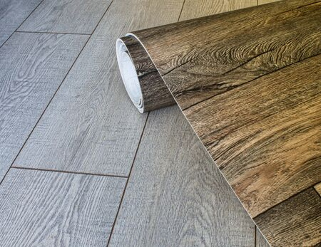 Roll of linoleum with a wood texture. Types of floor coverings. PVC.