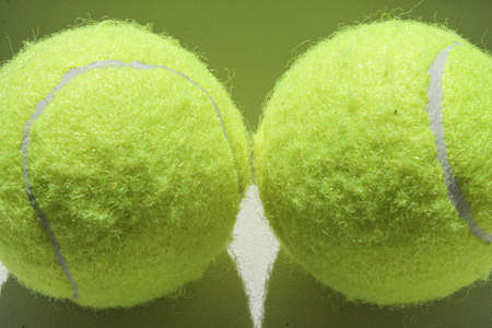 Two golden tennis balls on a white background