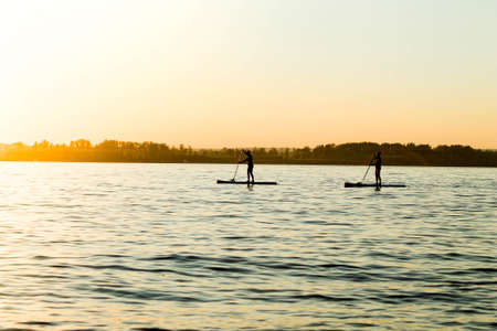 Stand-up surfing. Classes on the river at sunset.