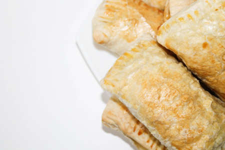 Fresh baked puff pastries on a white plate. Rich pastries on the table.