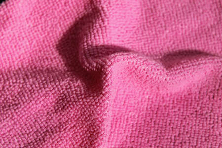 Pink microfiber napkin. Red cloth for the kitchen. Close-up.