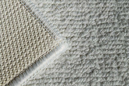 White rug for bathroom and toilet. Carpet texture with white overlock. Close-up.
