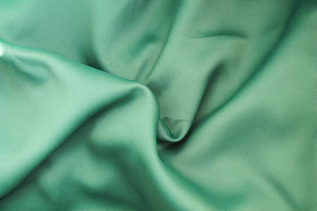 The fabric is green. The texture of the green fabric is wrinkled.