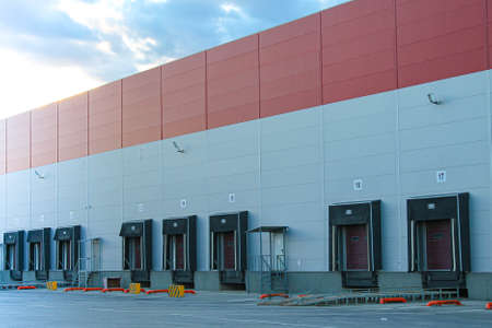 Warehouse complex outside with a gate for loading goods into the car. Warehouse for storing goods.