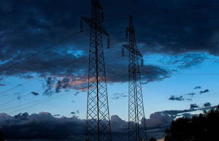 High voltage poles with wires on a dark background of the evening sky. Power lines.