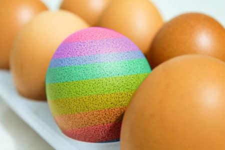 A multi-colored chicken egg among ordinary eggs in a tray. Archivio Fotografico