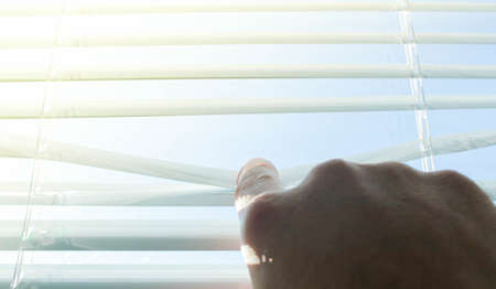 The sun shines through the half-open blinds on the window. Stockfoto