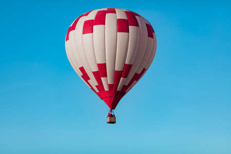 red white hot air balloon in the cloudless blue sky closeup Stock Photo