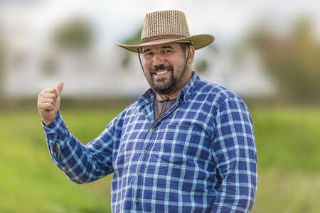 bearded brutal macho in cowboy hat ulybayutsya and happy life, full of positivity and optimism and is confident in the future and holding a thumb up