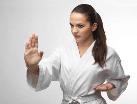 uniformes: Atractivos j�venes mujeres sexy en una actitud del karate aislados en blanco