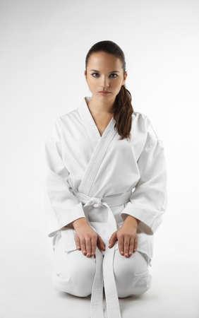 mujer deportista: Atractivos jóvenes mujeres sexy en una actitud del karate aislados en blanco