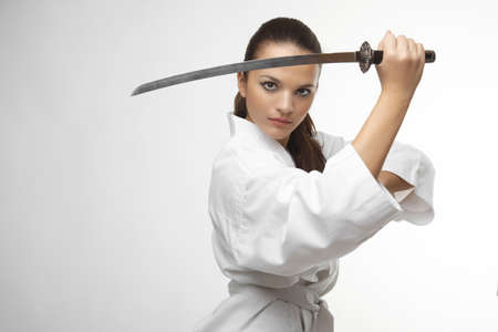 sensei: Attractive young sexy women with samurai sword on white background