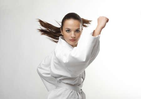 patada: Atractivos j�venes mujeres sexy en una actitud del karate aislados en blanco