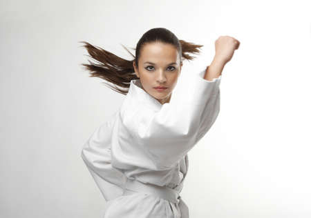 aikido: Attractive young sexy women in a karate pose isolated on white