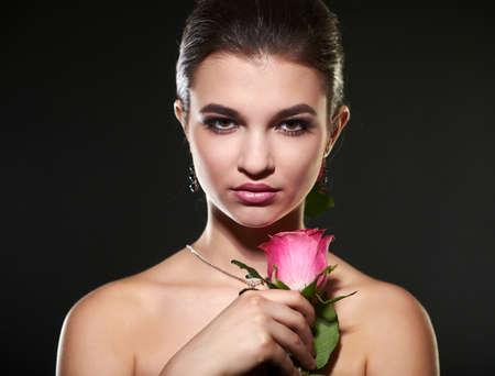 beautiful rose: female portrait with rose on black background Stock Photo