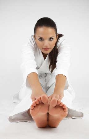 patada: Atractivos jóvenes mujeres sexy en una actitud del karate aislados en blanco
