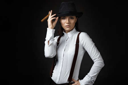 sexy lady: beautiful young woman in hat smoking cigarette