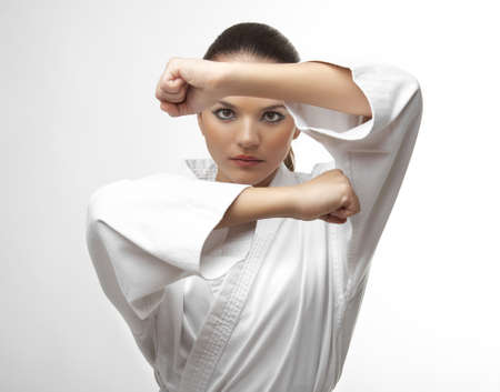 girl punch: Attractive young sexy women in a karate pose isolated on white