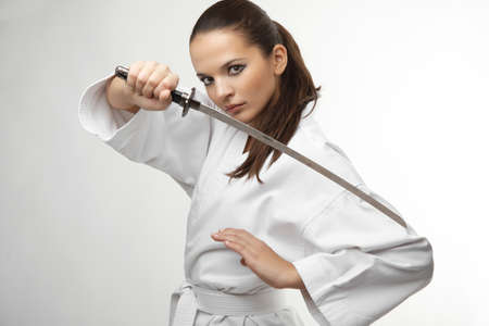 woman with sword: Attractive young sexy women with samurai sword on white background