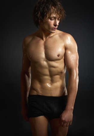 hombre desnudo: Hombre joven muscular sano en el fondo negro. Foto de archivo