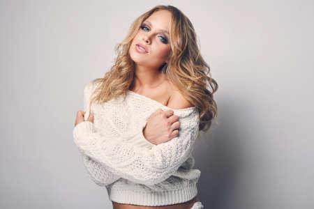 rubia: Retrato de la hermosa mujer rubia en blanco en el suéter blanco