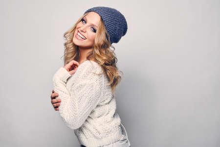 rubia: Retrato de la hermosa mujer rubia en blanco en el su�ter blanco y sombrero azul