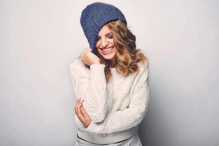 rubia ojos azules: Retrato de la hermosa mujer rubia en blanco en el su�ter blanco y sombrero azul