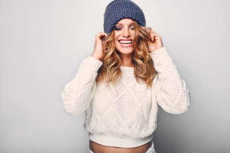Portrait der schönen blonden Frau in Weiß im weißen Pullover und blaue Hut