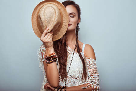 woman pose: Portrait of beautiful young hippie woman wearing hat in studio