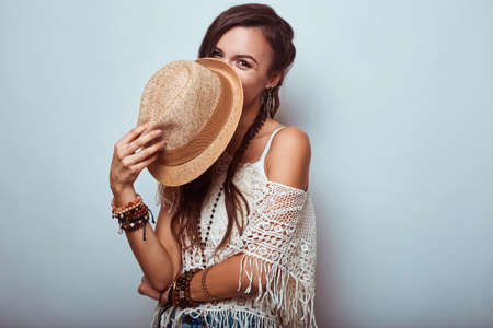 Portrait of beautiful young hippie woman wearing hat in studio