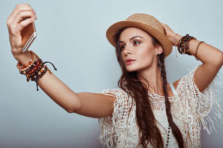 mujer hippie: Portrait of beautiful young hippie woman taking a selfie in studio Foto de archivo